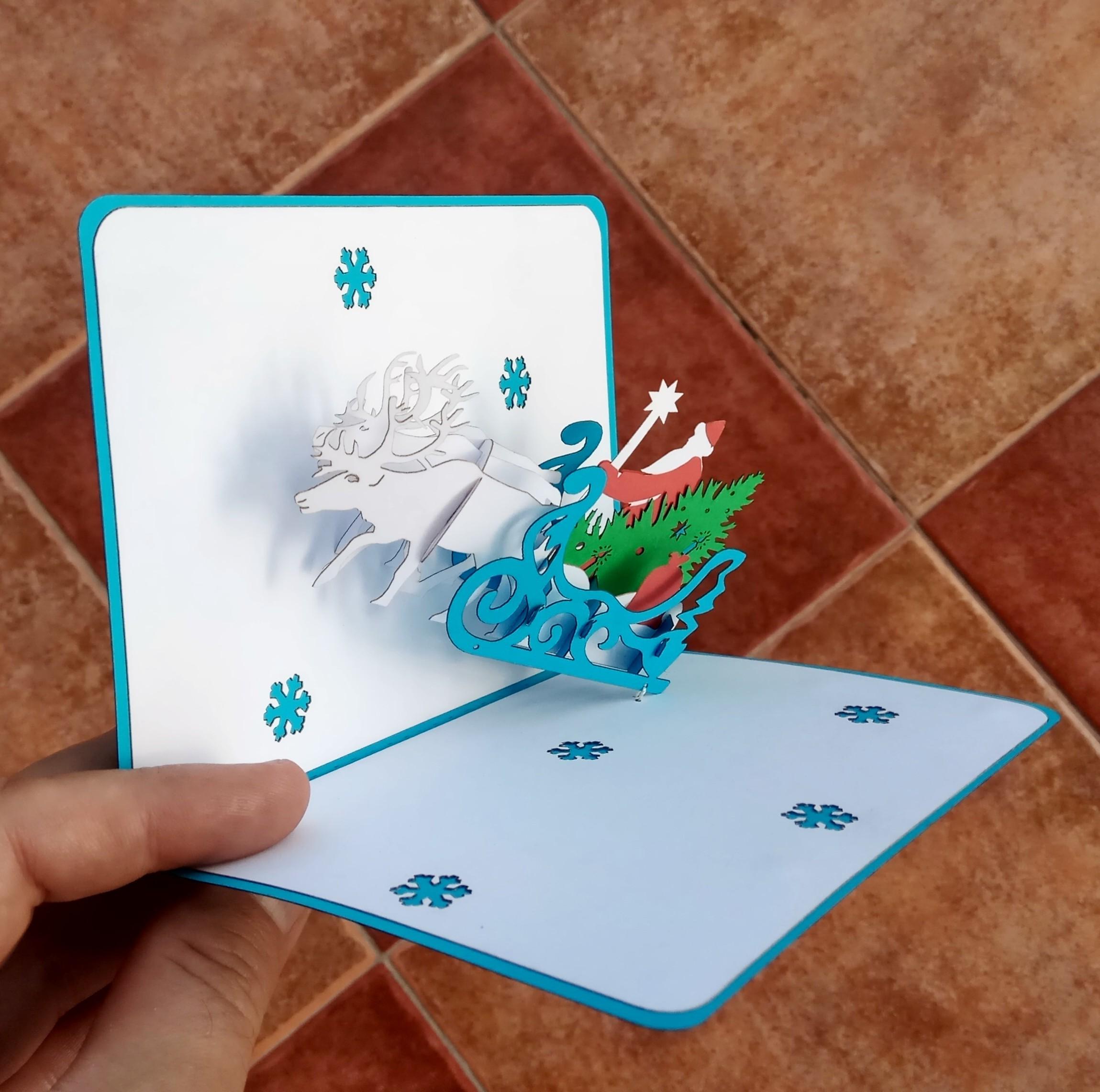 Новогодняя 3D открытка Дед Мороз в санях, запряжённых тремя северными оленям, с ёлкой и подарками.